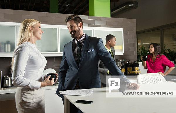 Junge Geschäftskollegen im Gespräch in der Büroküche