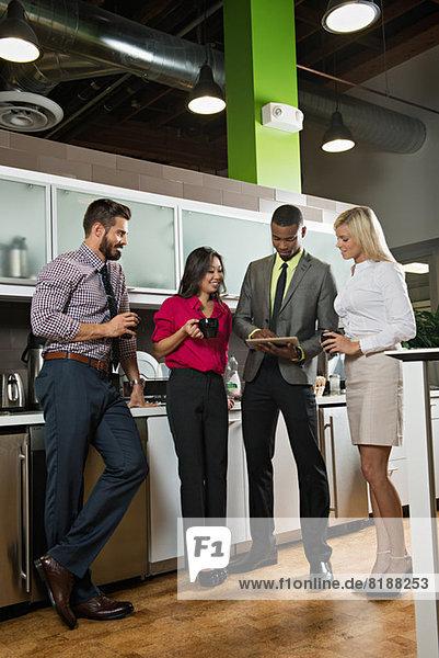 Junge Geschäftskollegen auf der Suche nach einer digitalen Tablet-Office-Küche