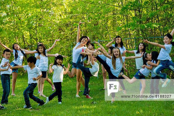 Große Gruppe von Kindern tanzen im Park