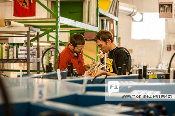 Mitarbeiter beim Prüfen von Farbmustern in der Siebdruckwerkstatt
