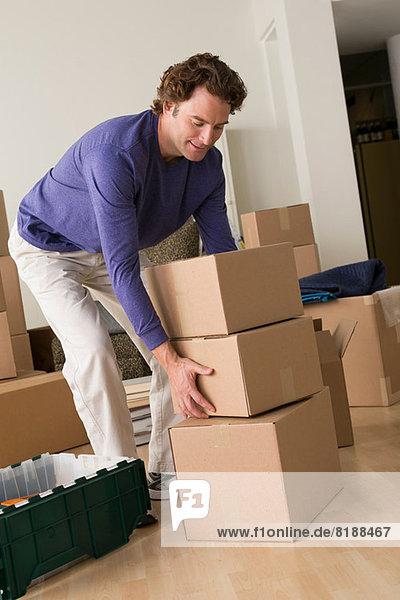 Erwachsener Mann bewegt Pappkartons