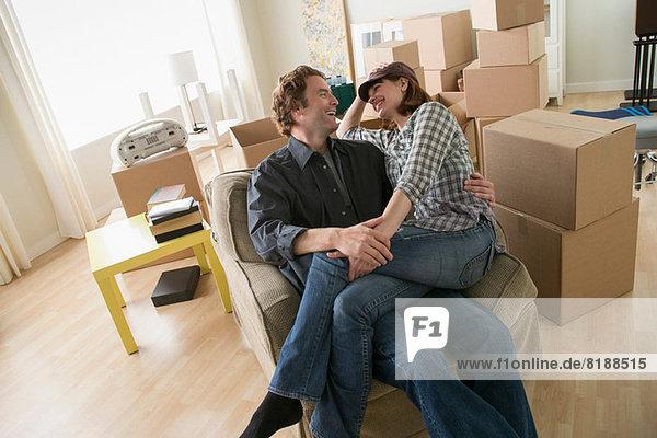Paar macht eine Pause im Sessel beim Umzug nach Hause