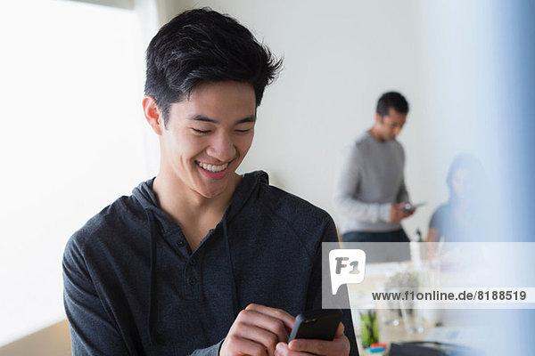 Männliche Büroangestellte texten auf dem Handy