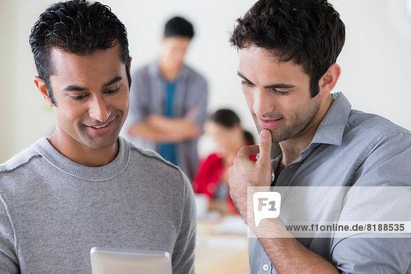 Junge männliche Kollegen im Büro im Gespräch