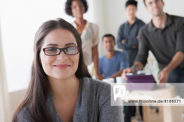 Porträt einer jungen Büroangestellten vor Kollegen