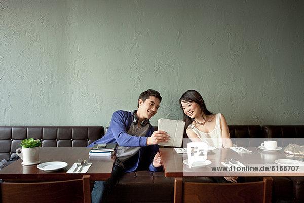 Junger Mann zeigt junge Frau digitales Tablett im Restaurant