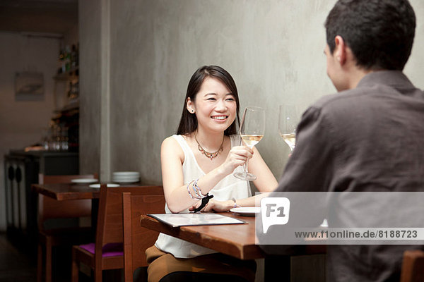 Young couple toasting white wine in restaurant