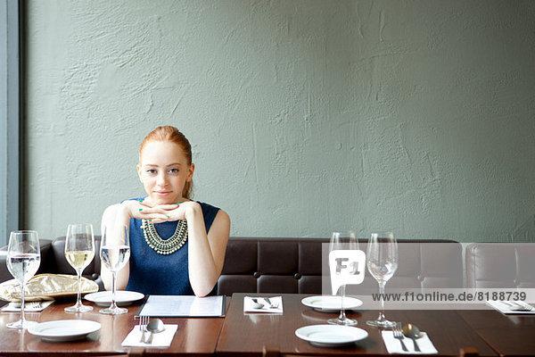 Junge Frau im Restaurant  Hände am Kinn