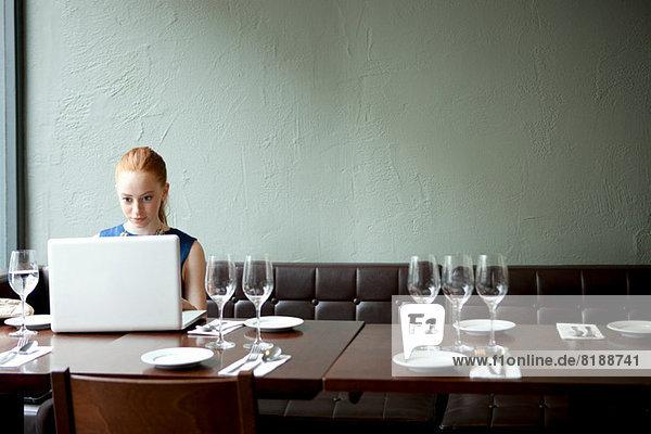 Junge Frau mit Laptop im Restaurant