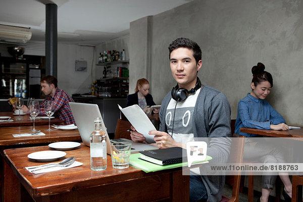 Junger Mann mit Laptop im Café