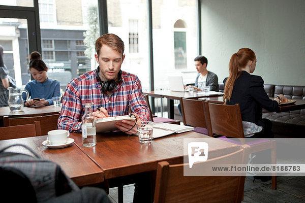 Junger Mann mit digitalem Tablett im Café
