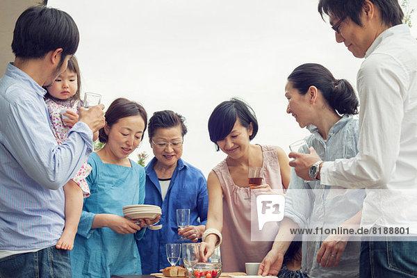 Drei Generationen Familie beim Essen im Freien