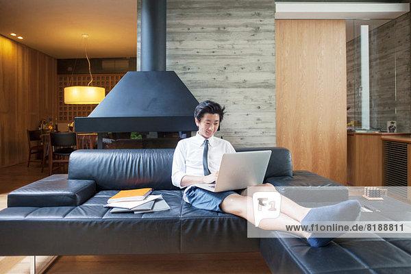 Teenager Junge mit Laptop auf dem Sofa
