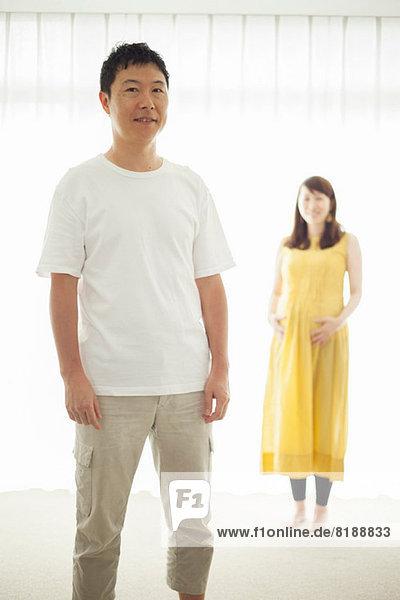 Mann mit schwangerer Frau im Hintergrund  Portrait