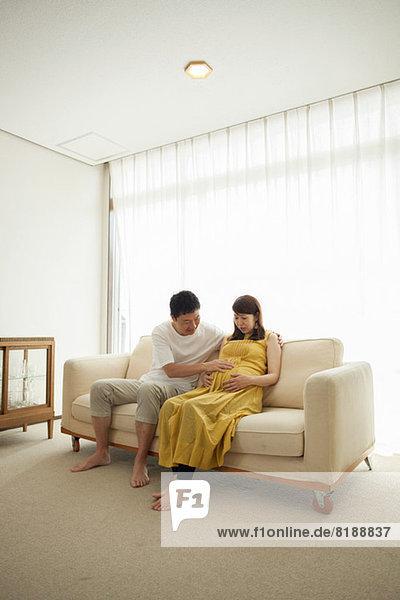 Mann berührt den Bauch einer schwangeren Frau auf dem Sofa