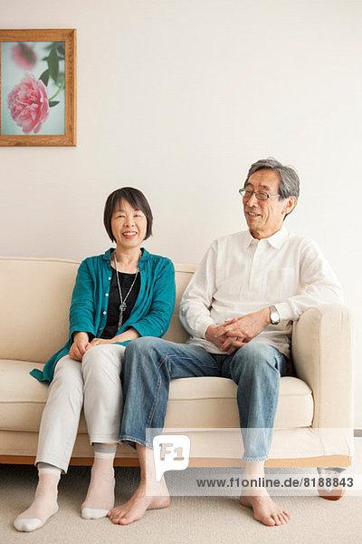 Seniorenpaar auf Sofa sitzend  Portrait