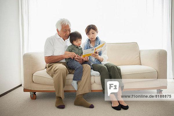 Mutter liest dem Sohn vor  der auf Großvaters Schoß sitzt.