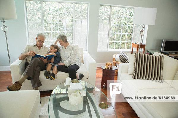 Großeltern zeigen Jungen-Fotoalbum auf Sofa
