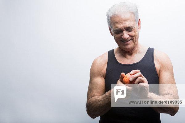Senior Mann mit Apfel  lächelnd