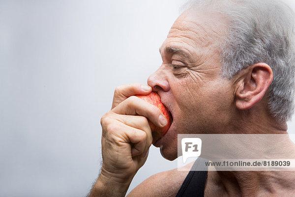 Senior man eating apple  close up