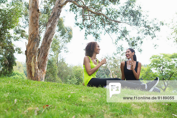 Mid adult and young woman relaxing in park