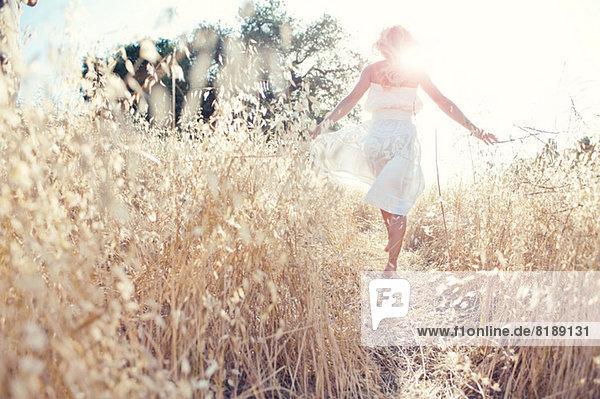 Frau geht durchs Feld und berührt Gräser