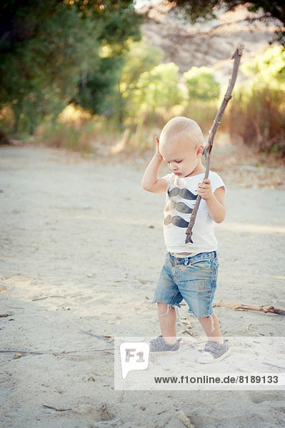 Young male toddler with stick