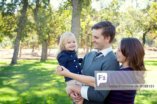 Young parents in park holding female toddler