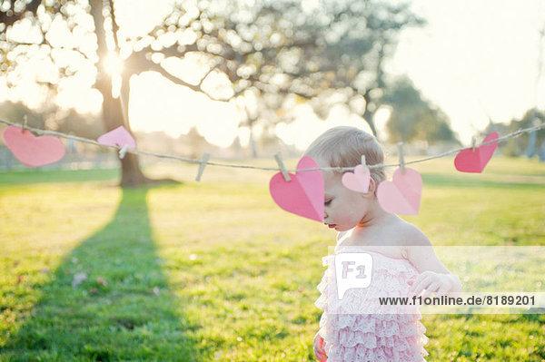 Junges Mädchen neben Herzformen auf der Wäscheleine Junges Mädchen neben Herzformen auf der Wäscheleine