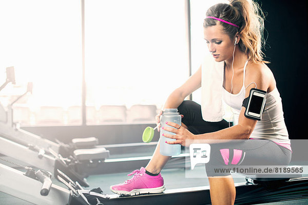Junge Frau mit Wasserflasche im Fitnessstudio