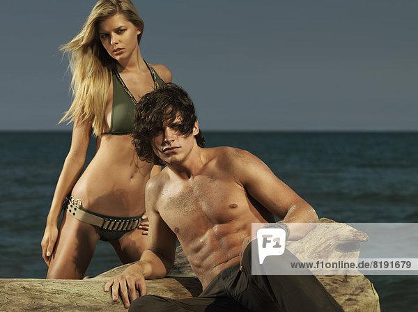 Frau in einem Bikini im Militär-Stil  mit einem Mann am Strand