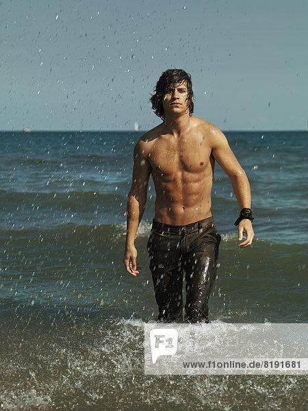 Mann mit nackter Brust und langer Hose  aus dem Meer kommend