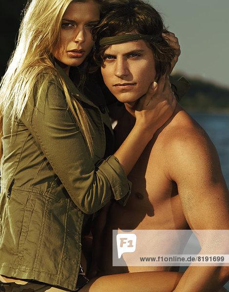 Liebespaar am Strand  Mann hält Frau auf seinen Armen