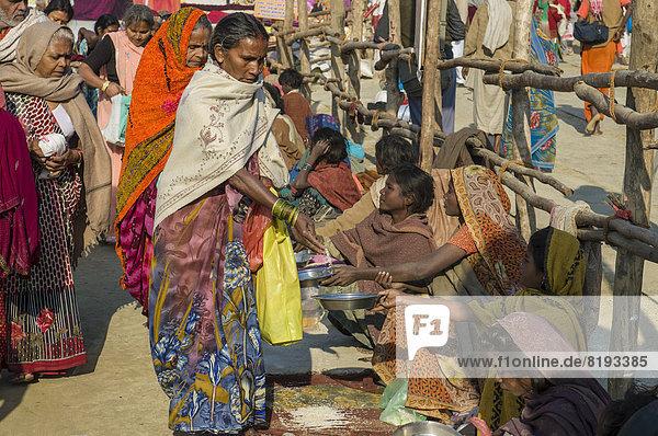 Bettler sitzen in einer Reihe  während der Kumbha Mela
