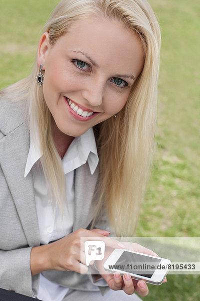 benutzen  Portrait  Geschäftsfrau  Fröhlichkeit  Rasen  Telefon  jung  schlau