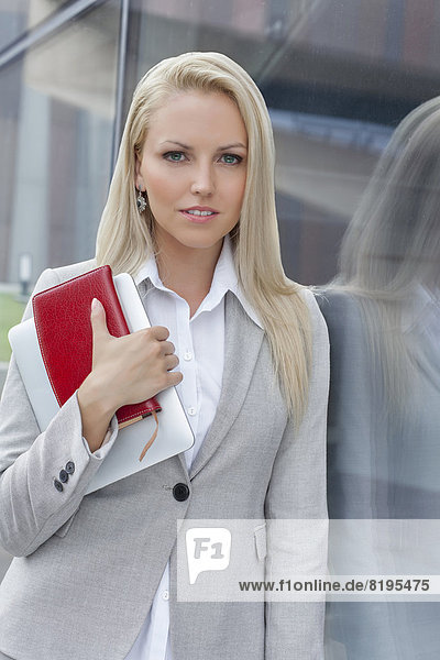 Portrait of beautiful businesswoman holding organizer and digital tablet while leaning on glass wall