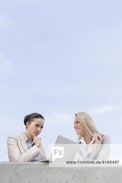 niedrig  stehend  benutzen  Geschäftsfrau  Notebook  Konzentration  Himmel  Ansicht  Flachwinkelansicht  Terrasse  Kollege  Winkel
