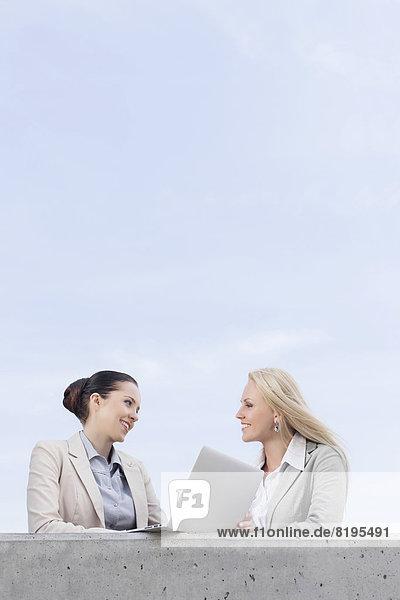 niedrig  stehend  Geschäftsfrau  Fröhlichkeit  Diskussion  Notebook  Himmel  Ansicht  jung  Flachwinkelansicht  Terrasse  Winkel