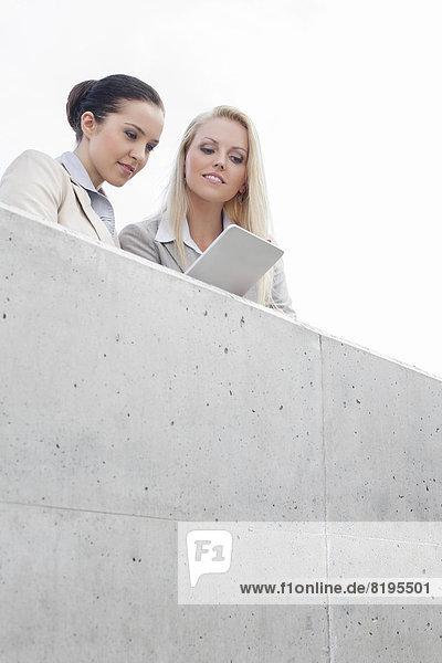 niedrig  stehend  Zusammenhalt  benutzen  Geschäftsfrau  Himmel  Ansicht  jung  Flachwinkelansicht  Tablet PC  Terrasse  Winkel