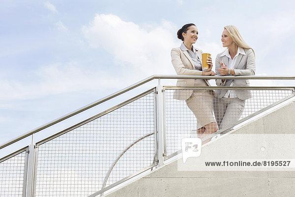 niedrig  stehend  Geschäftsfrau  Fröhlichkeit  Diskussion  Himmel  Ansicht  Flachwinkelansicht  Geländer  Winkel