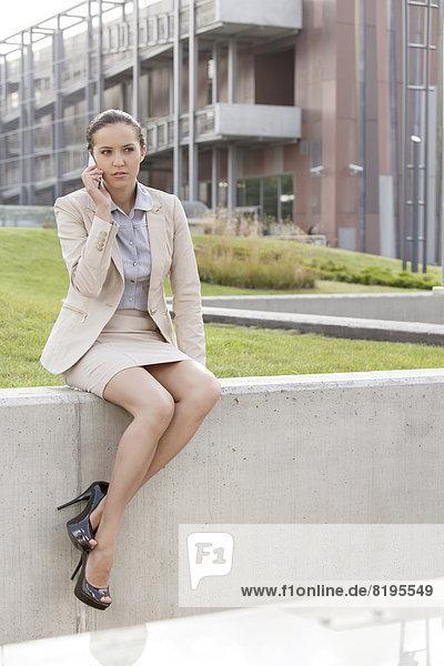 sitzend  benutzen  Geschäftsfrau  Handy  Wand  Gebäude  Telefon  Büro  jung  Länge  voll