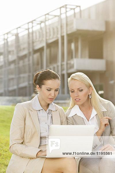 sitzend  Zusammenhalt  benutzen  Geschäftsfrau  Notebook  Gebäude  Büro  jung