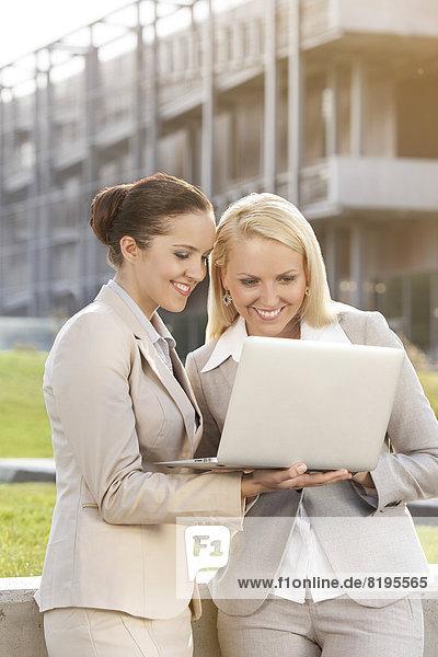 Zusammenhalt  benutzen  Geschäftsfrau  Fröhlichkeit  Notebook  Gebäude  jung