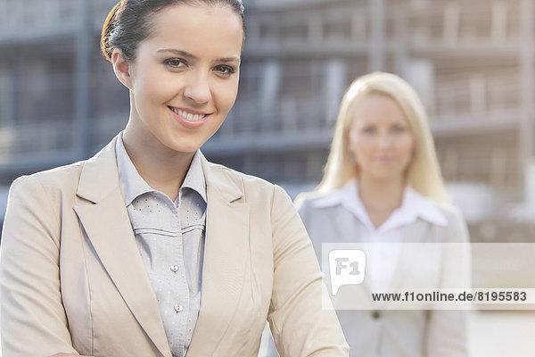 Portrait  Geschäftsfrau  Fröhlichkeit  Kollege  Hintergrund  jung
