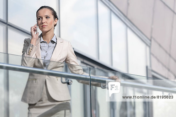 Confident young businesswoman using cell phone at office balcony