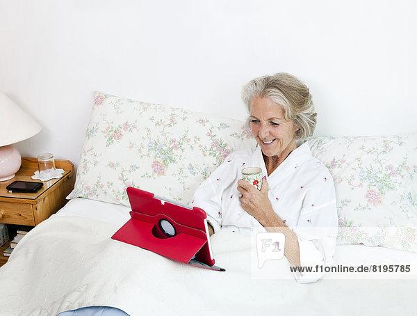Interior  zu Hause  Senior  Senioren  benutzen  Frau  Fröhlichkeit  Bett  Tablet PC  Kaffee