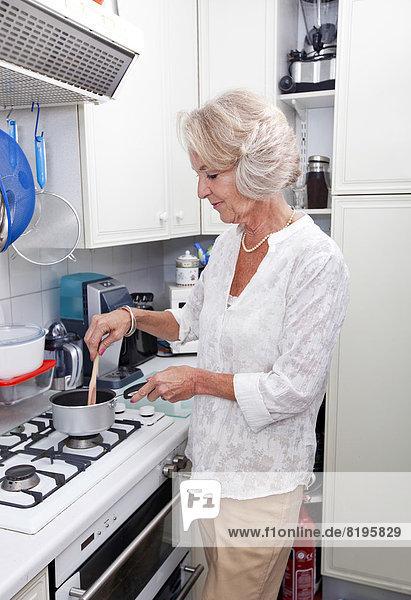 Senior Senioren kochen Frau Küche Tresen