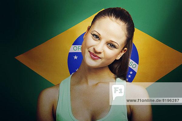 Lächelnde junge Frau steht vor brasilianischer Flagge