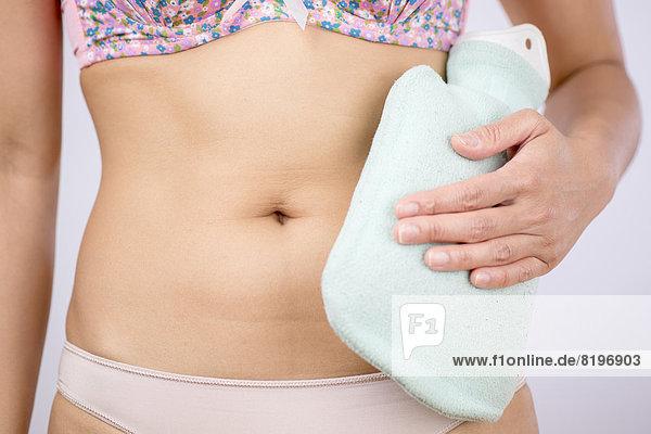 Mittlere erwachsene Frau mit heißem Wassersack auf dem Bauch  Nahaufnahme