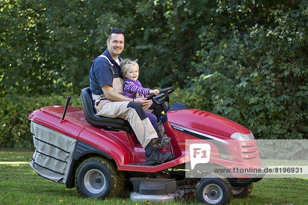 Kleinkind mit Vater auf Rasenmäher